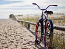 Bike leaning on wood rail along beach